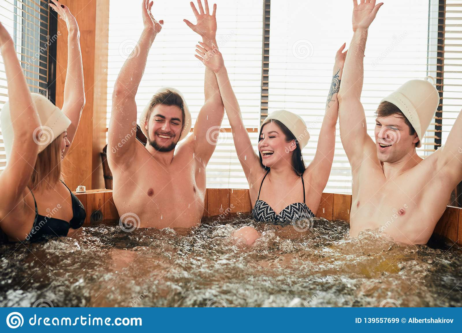 Group of caucasian diverse friends enjoying jacuzzi in hotel spa