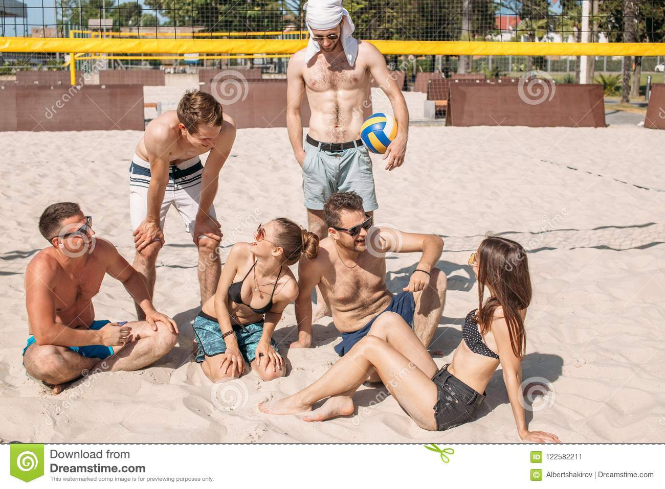 Group of caucasian friends resting at interval between sets on beach court.
