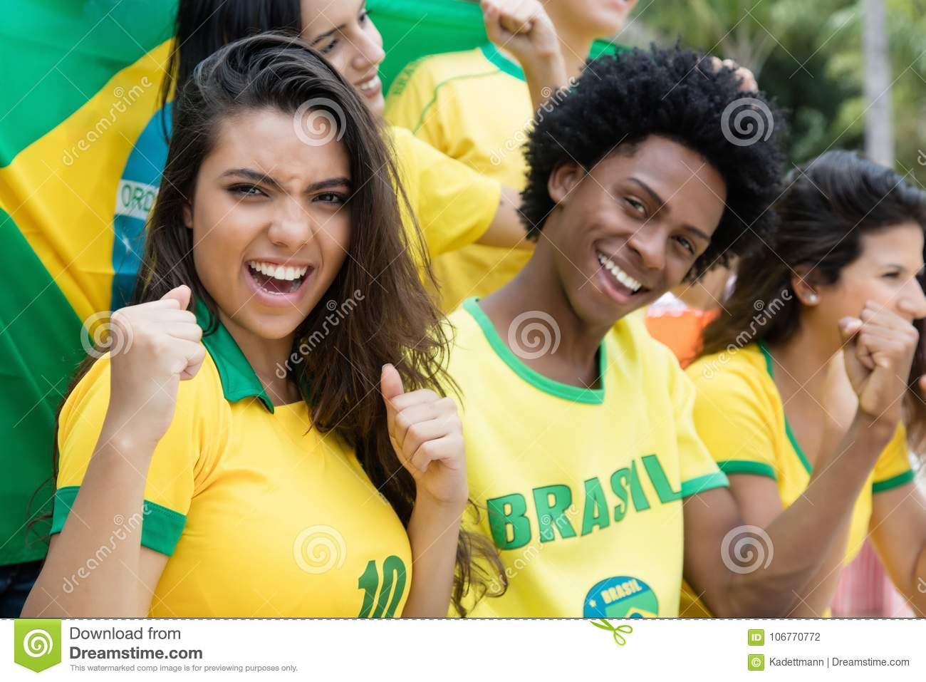 Group of cheering brazilian soccer fans with flag of brazil