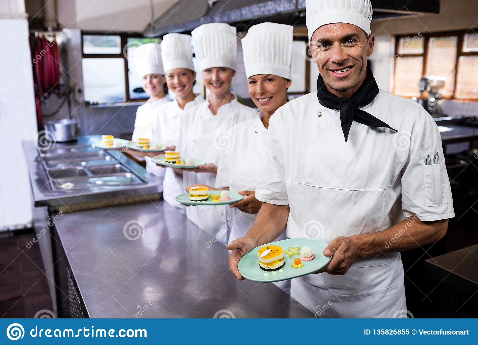 Group of chefs holding plate of delecious desserts in kitchen