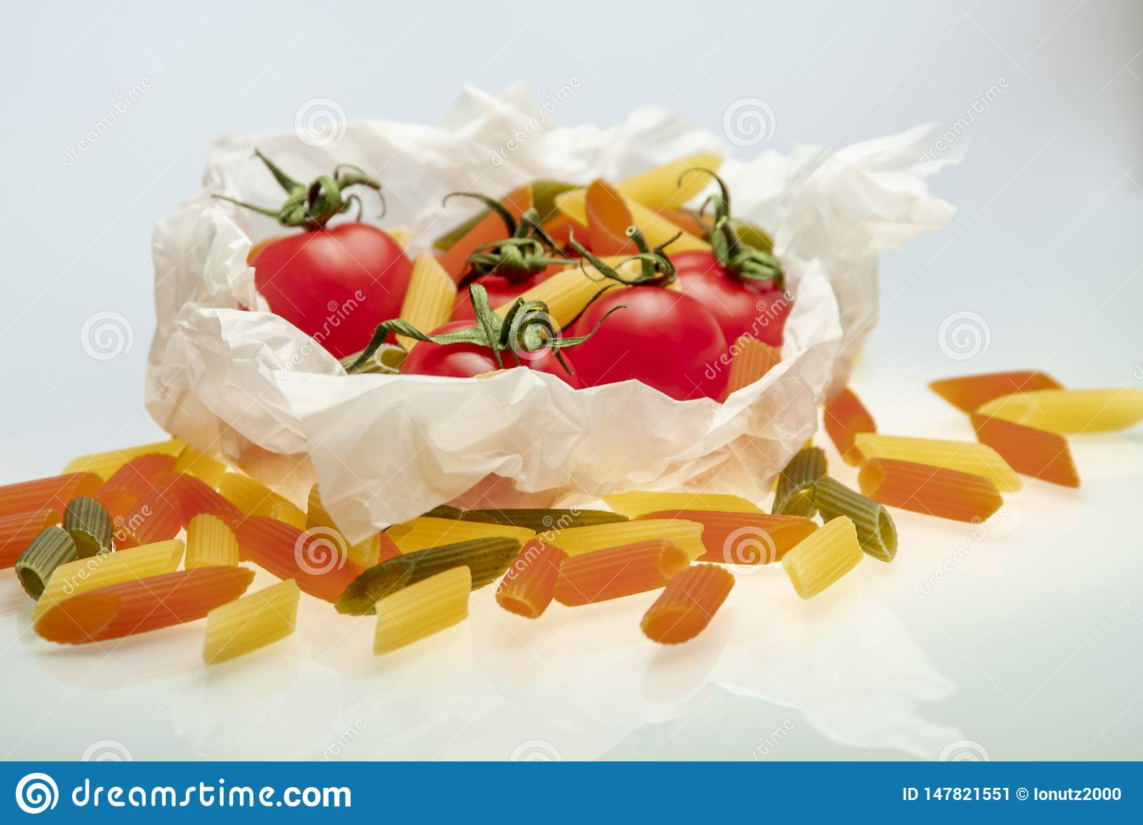 Group of cherry tomatoes and colored pasta wrapped in cooking paper
