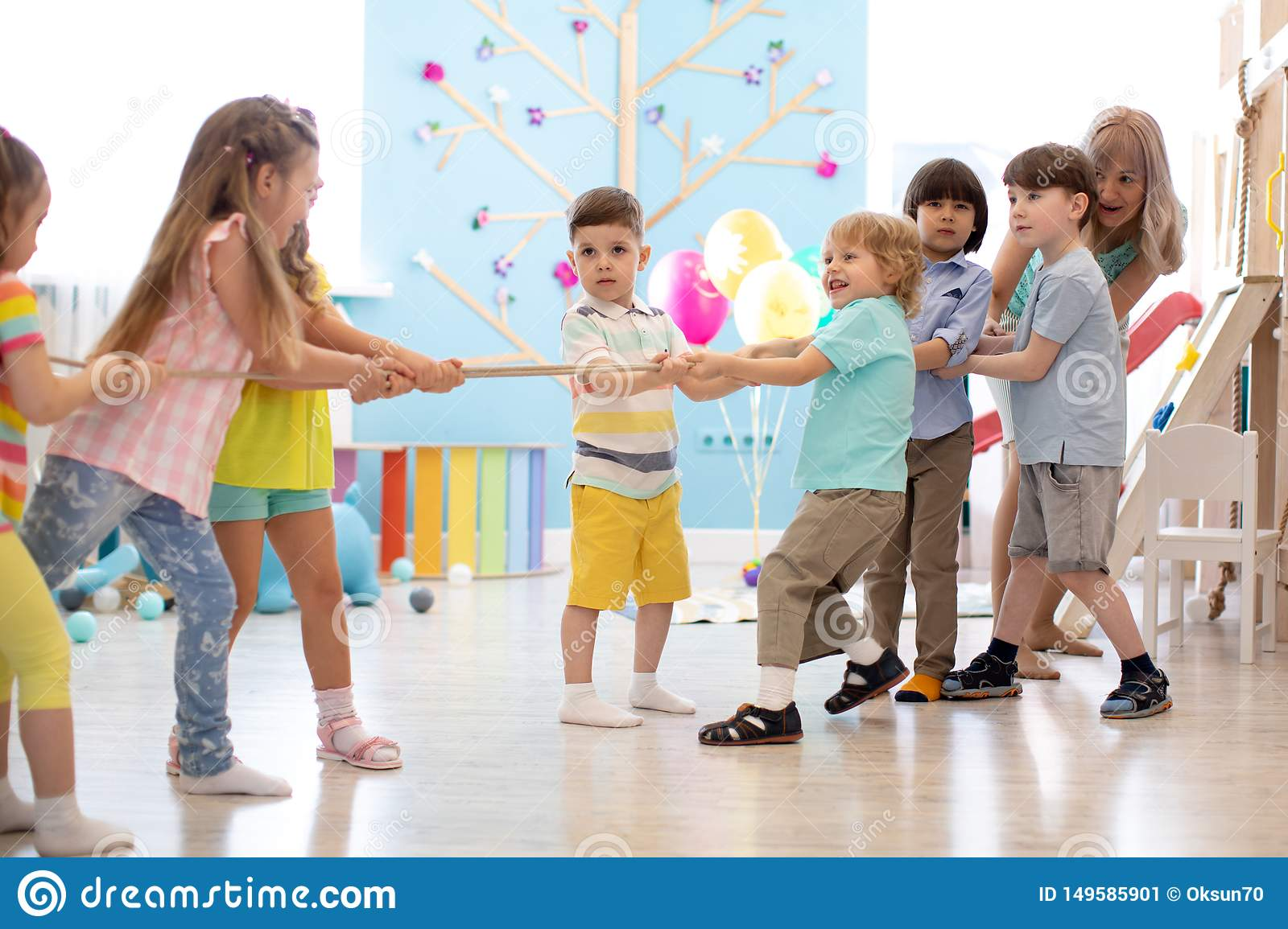 Group of children in a rope-pulling contest in kindergarten