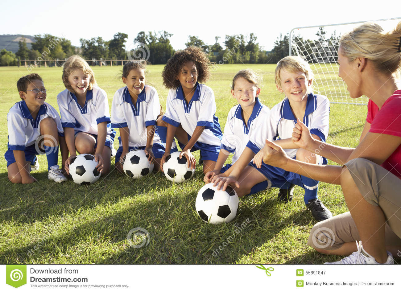 Group Of Children In Soccer Team Having Training With ...