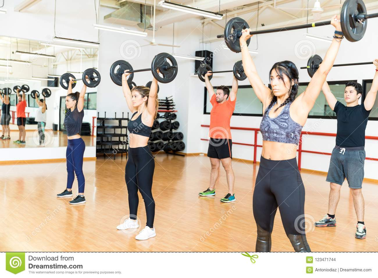 Determined Men And Women Lifting Barbells In Gym