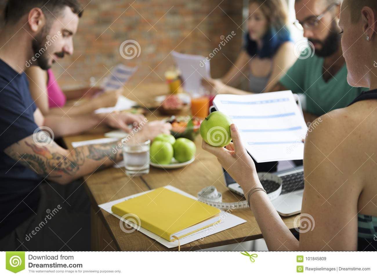A group of diverse healthy people studying health form together