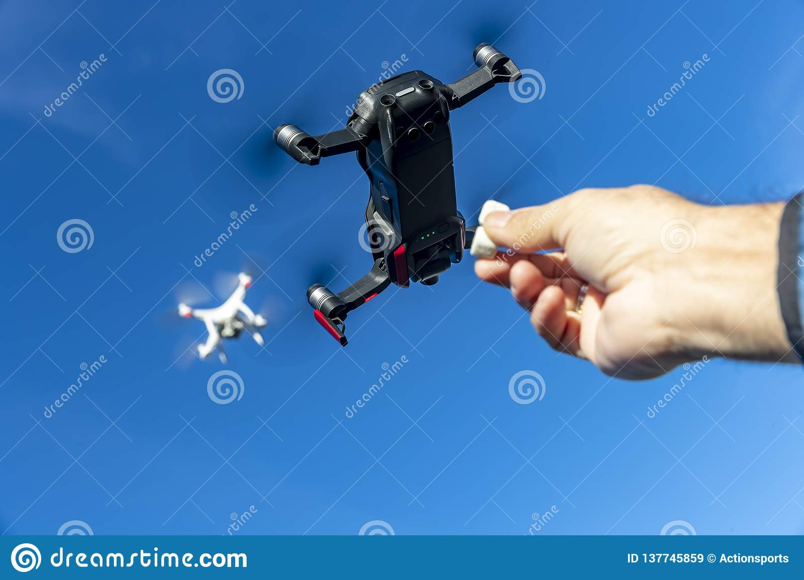 A Group Of Multiple Drones Fly Together Through The Air Against A Blue Sky Waiting To Be Fed