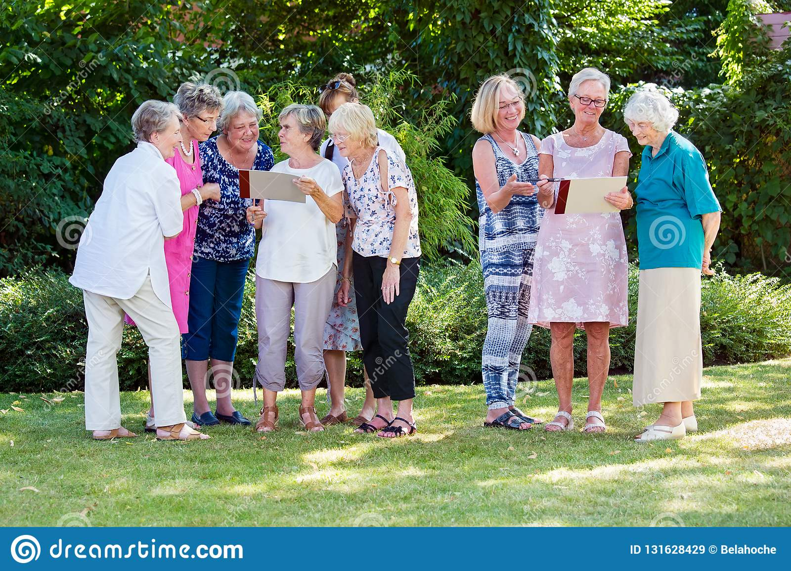 Group of elderly ladies at a care home enjoying a stimulating creative art class outdoors in a garden or park.