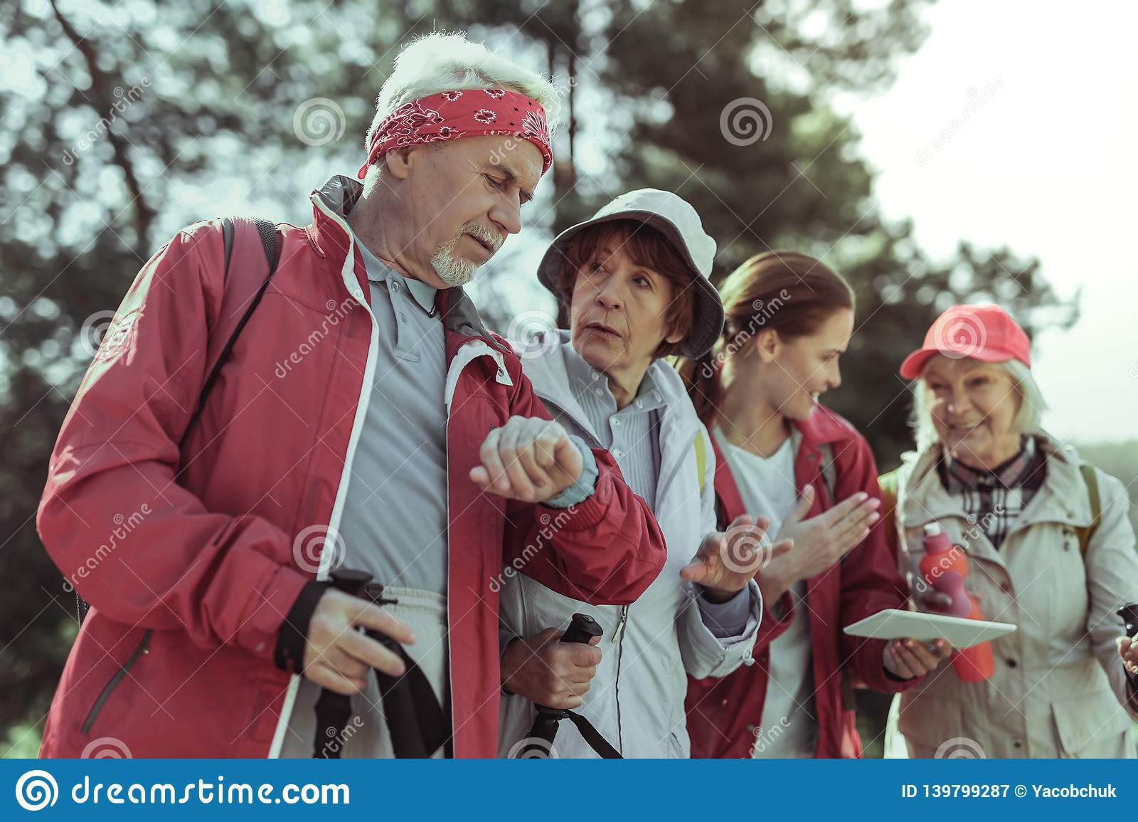 Group of elderly tourists checking time and direction