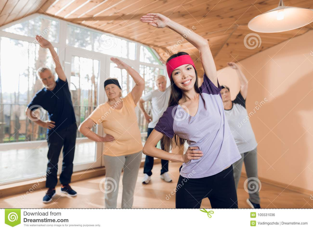 A Group Of Elderly Women And Men Doing Therapeutic Gymnastics In A Nursing Home