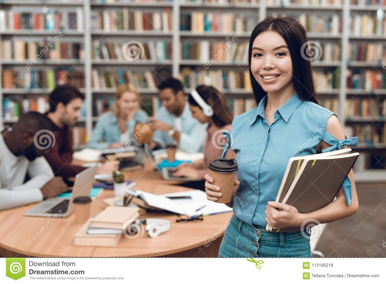 Group of ethnic multicultural students in library. Asian girl with notes and coffee.