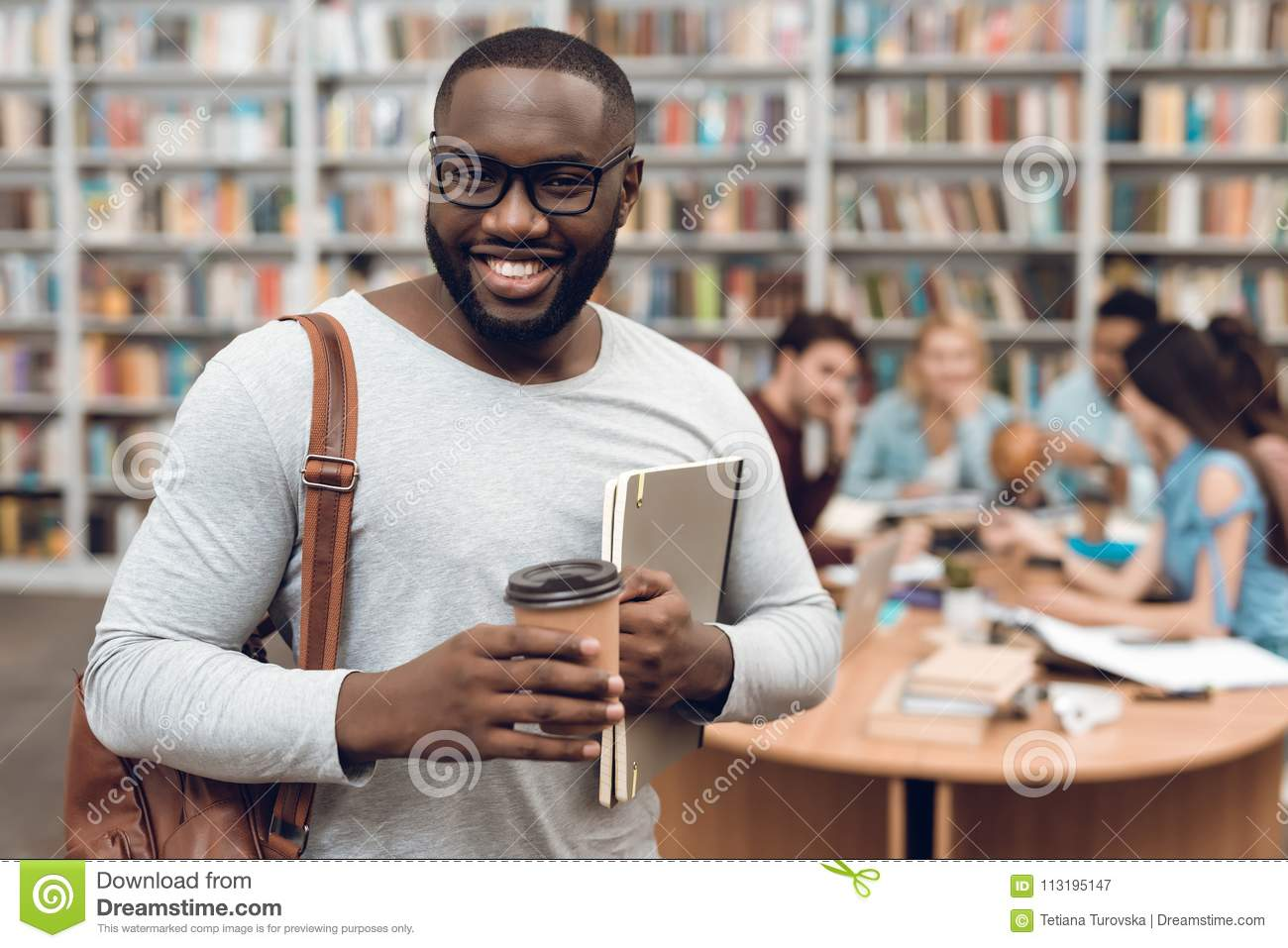 Group of ethnic multicultural students in library. Black guy with notes and coffee.