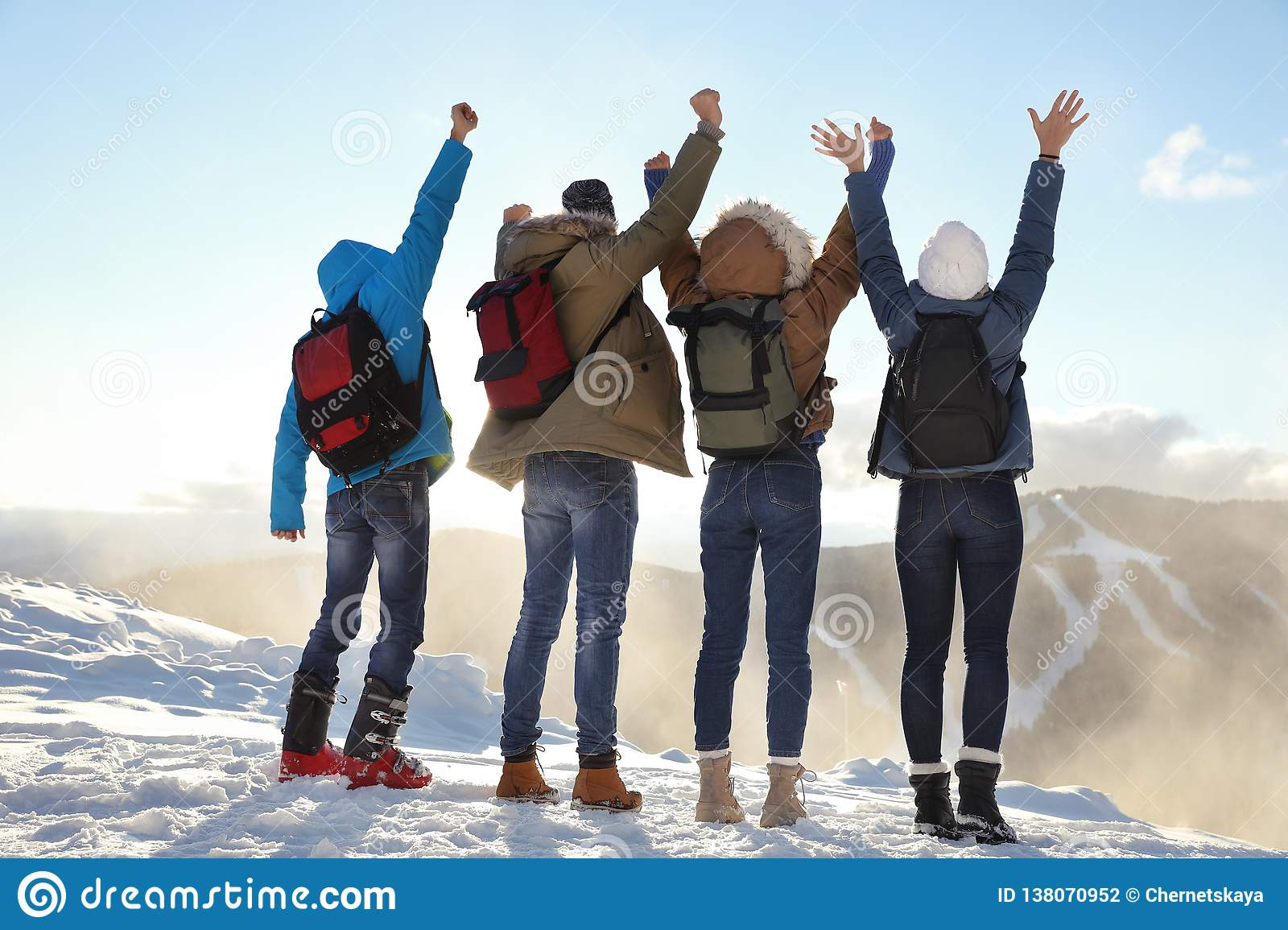 Group of excited friends with backpacks enjoying view during winter vacation