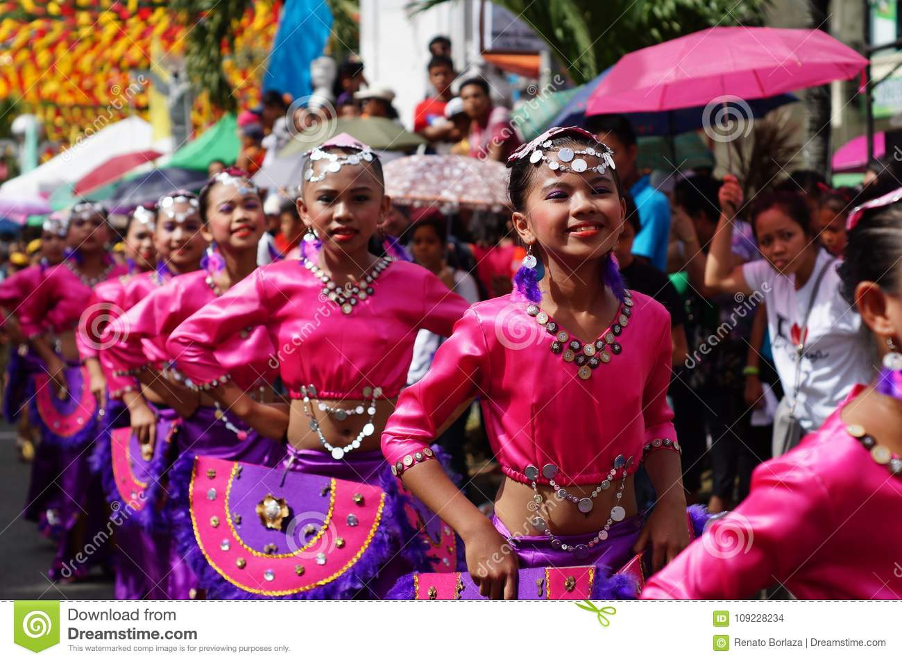 A group of carnival dancers in various costumes dance in delight.
