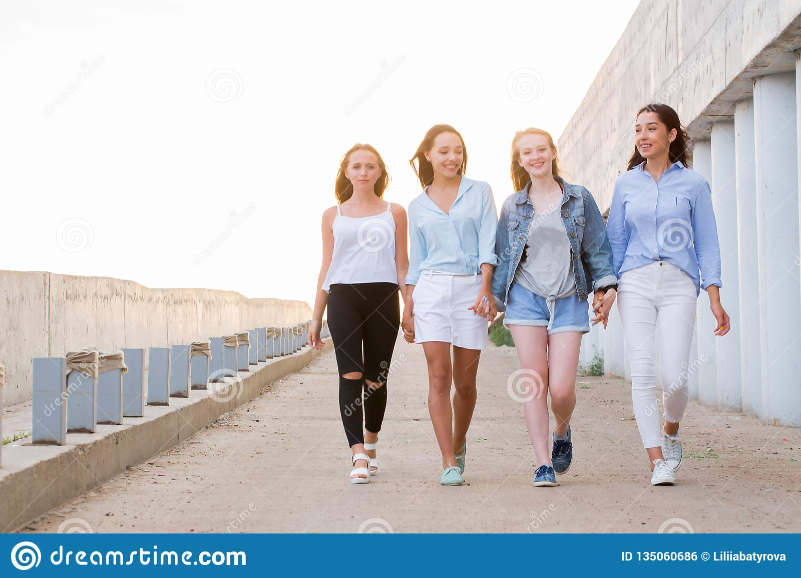 Group of female friends walking outdoor, talking, having fun and smile. togethernes, friendship, lifestyle concept