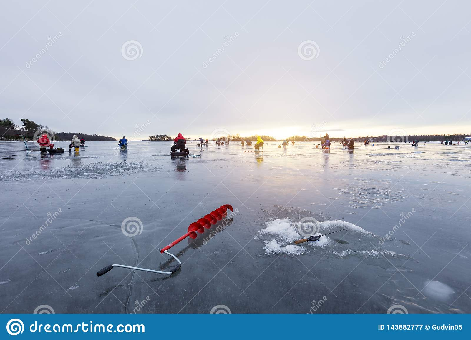 Group of fishermens on winter fishing on ice at sunset