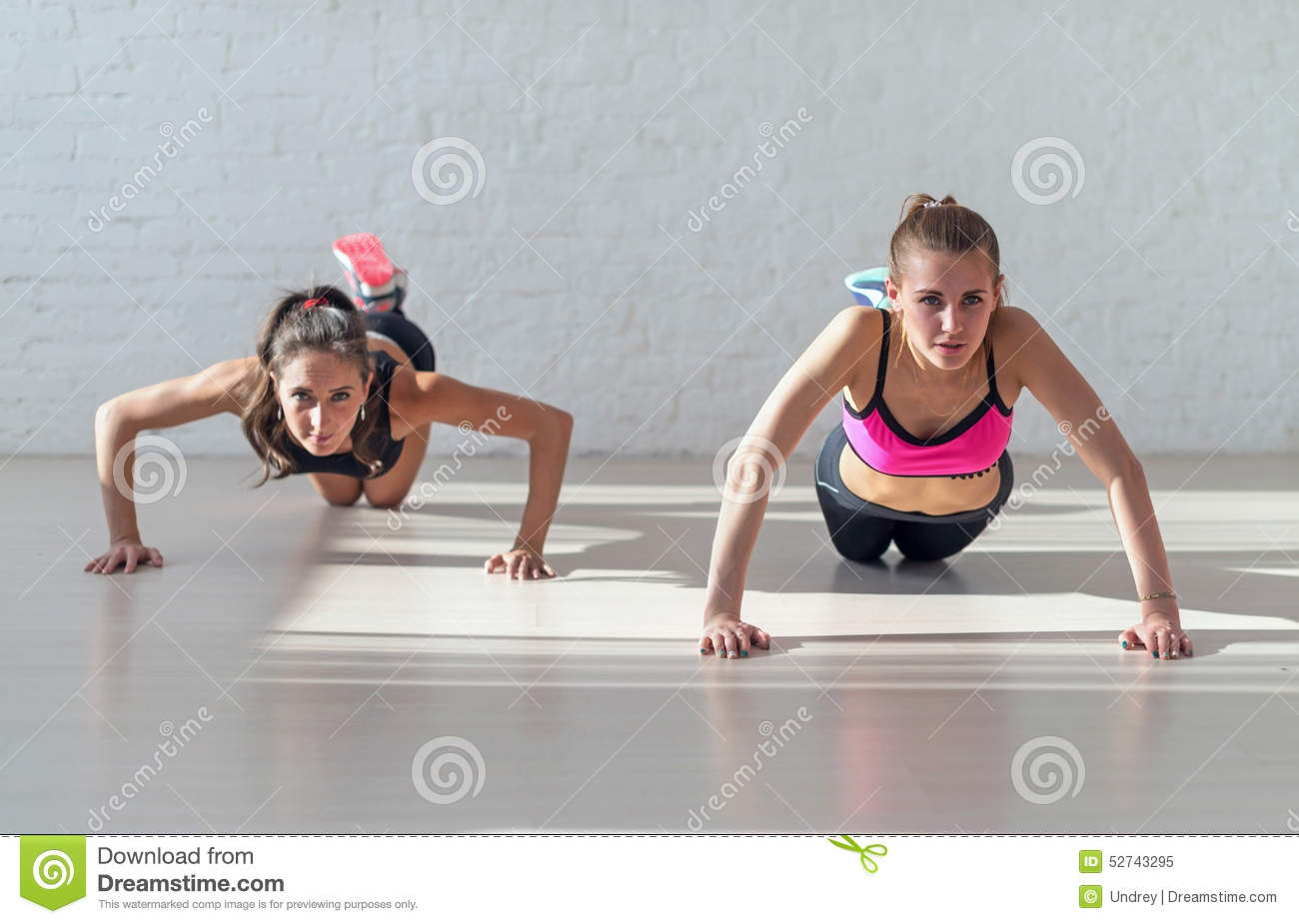 Group of fit women warming up and doing push ups