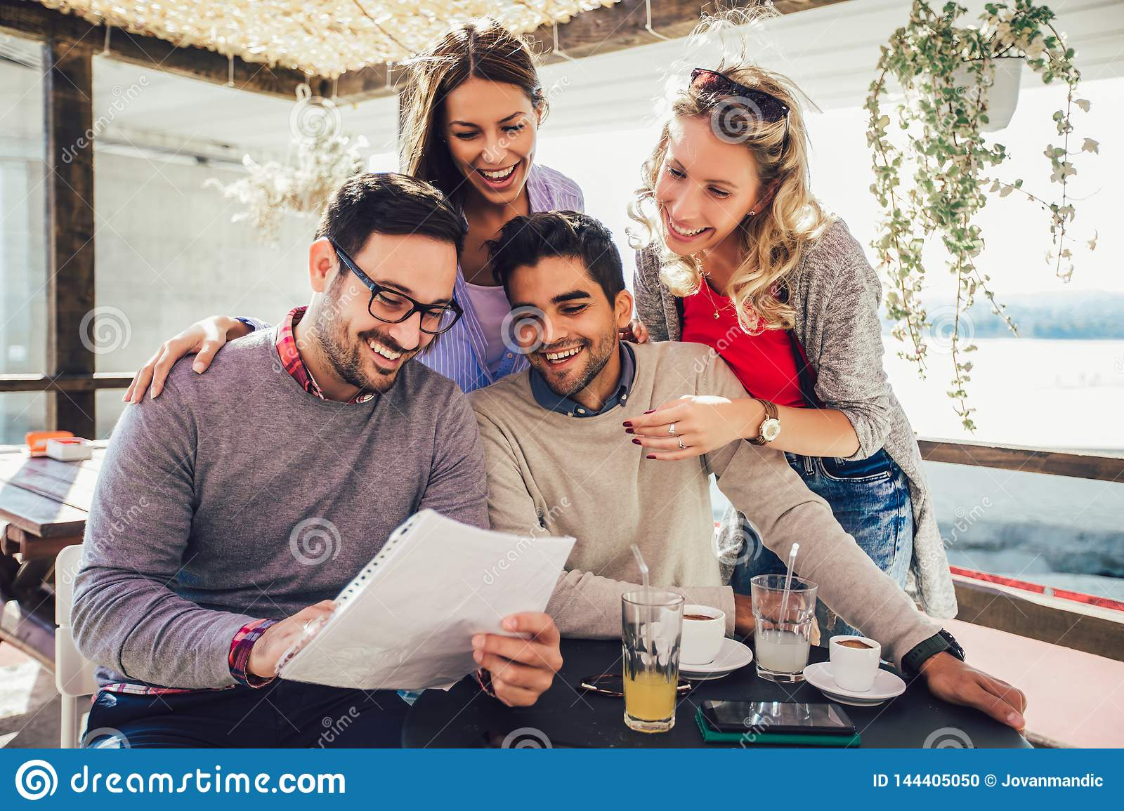Group of four friends having fun a coffee together.