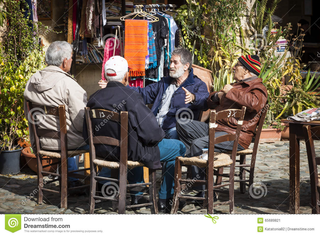 Group of four old male friends talking in city park