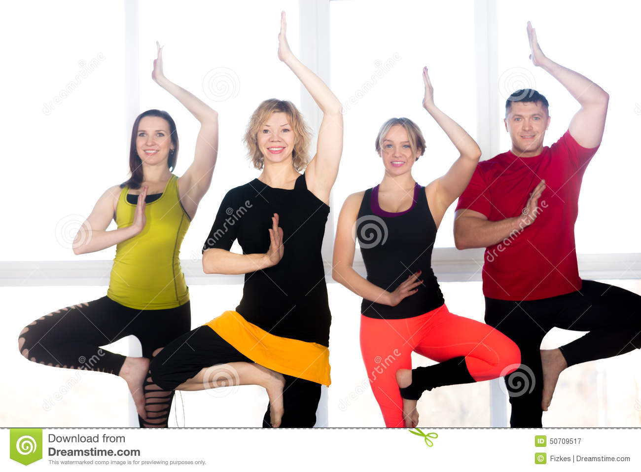 Group Of Four Positive People Doing Yoga Practice In Class Stock