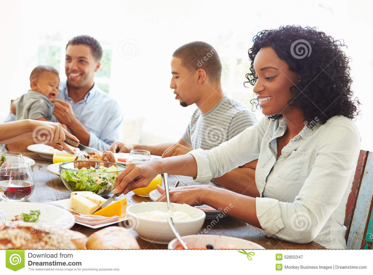 Group Of Friends With Babies Enjoying Meal At Home Together
