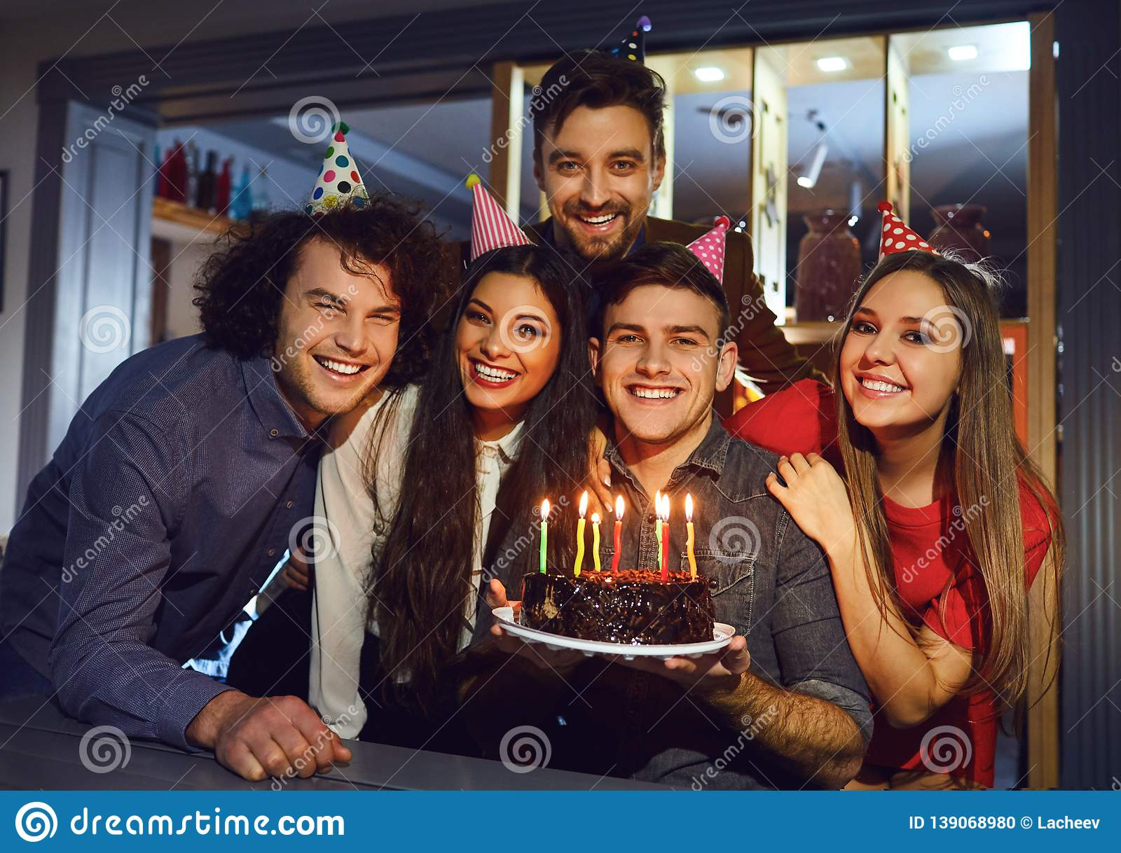 Group of friends celebrating birthday with birthday cake at restaurant