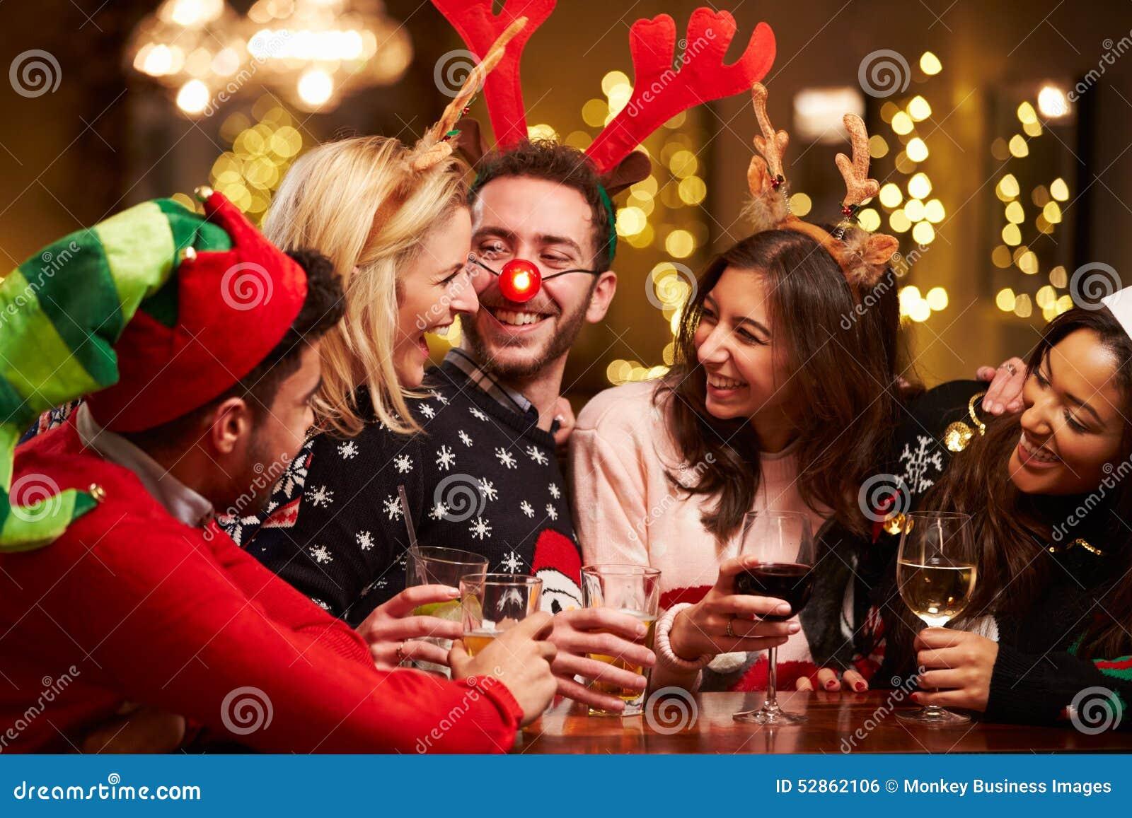 Group of friends enjoying christmas drinks in bar stock