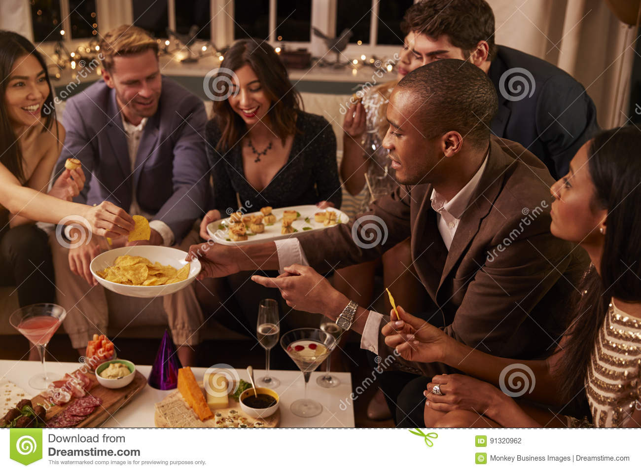 Group Of Friends Enjoying Drinks And Snacks At Party