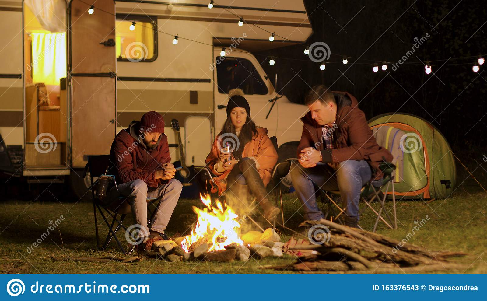 Group Of Friends Gathered Around Camp Fire In A Cold Night ...