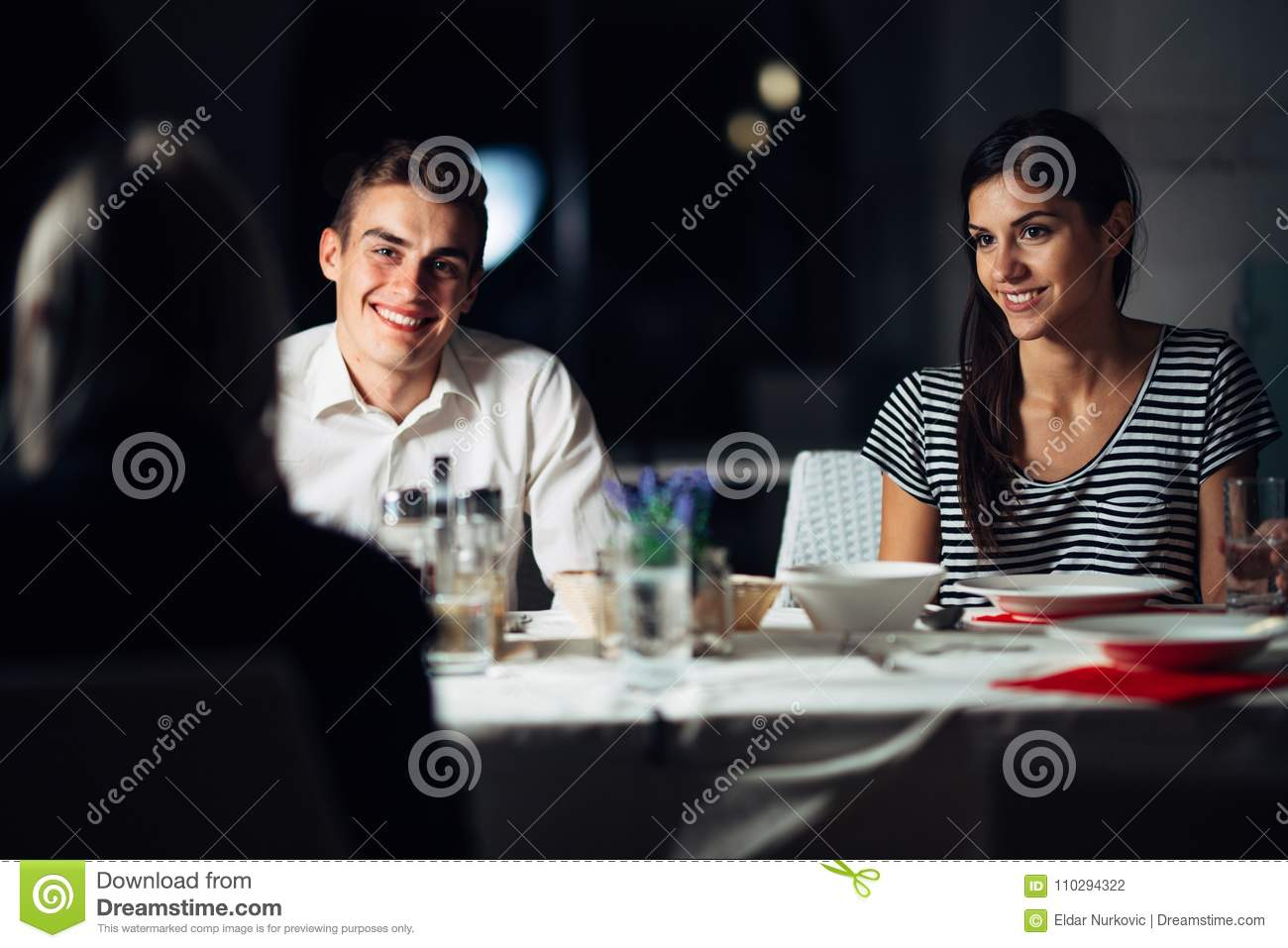 Group of friends having a dinner in a restaurant.Double date.Attractive people night out,dining in a hotel.Trendy people