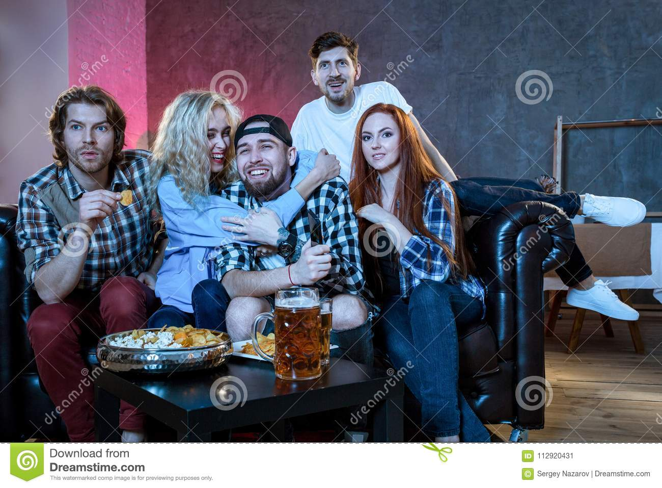 Group of friends having fun at home,watching game and enjoying t