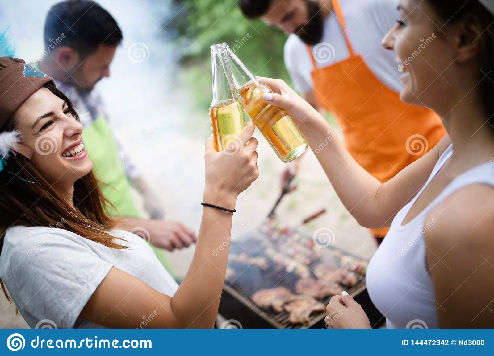 Group of friends having a picnic in a park outdoor. Happy young people enjoying bbq