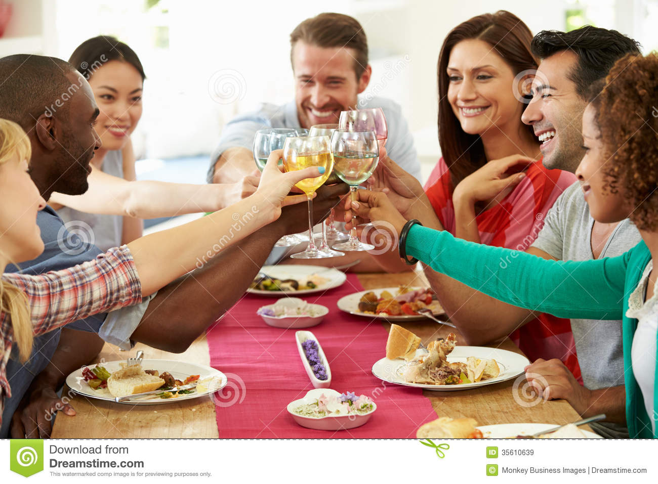 group of friends making toast around table at dinner party stock