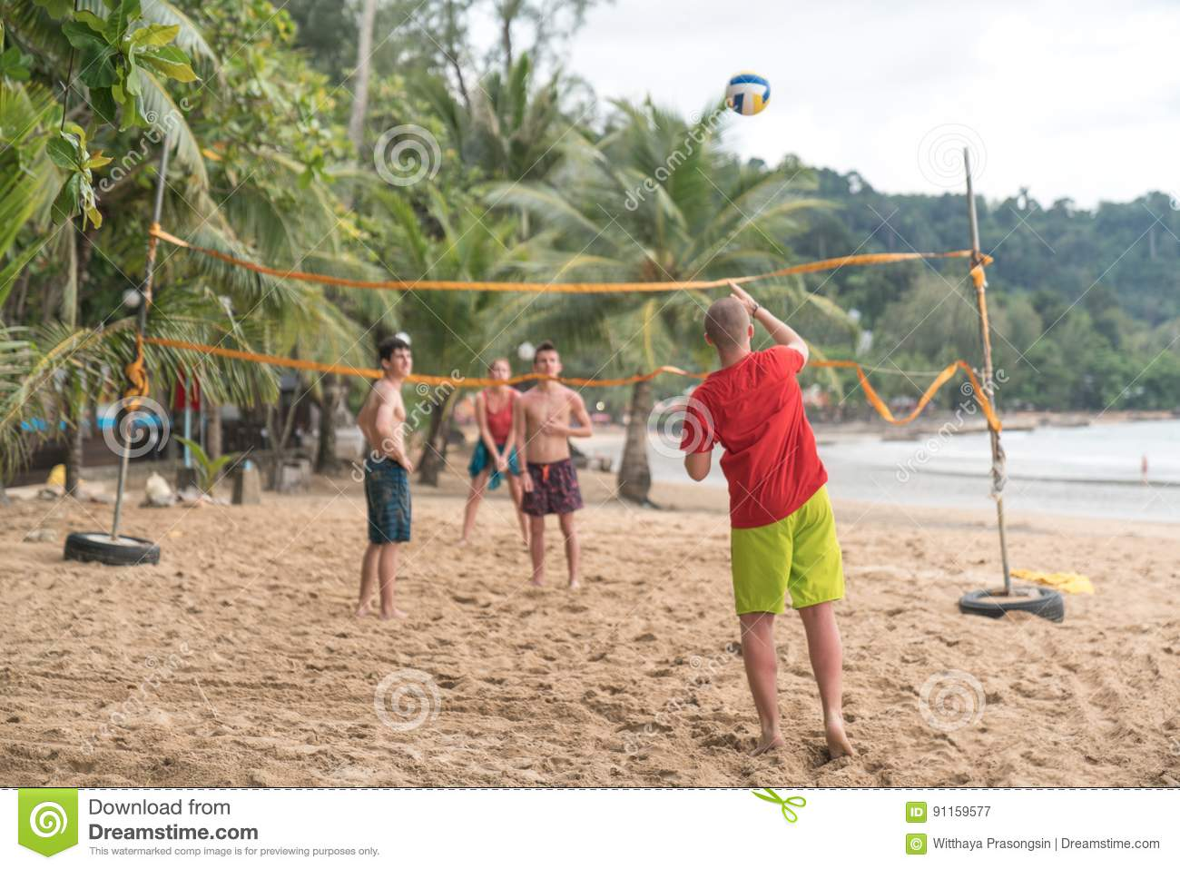 Group of friends playing beach volley - Multi-ethic group of peo