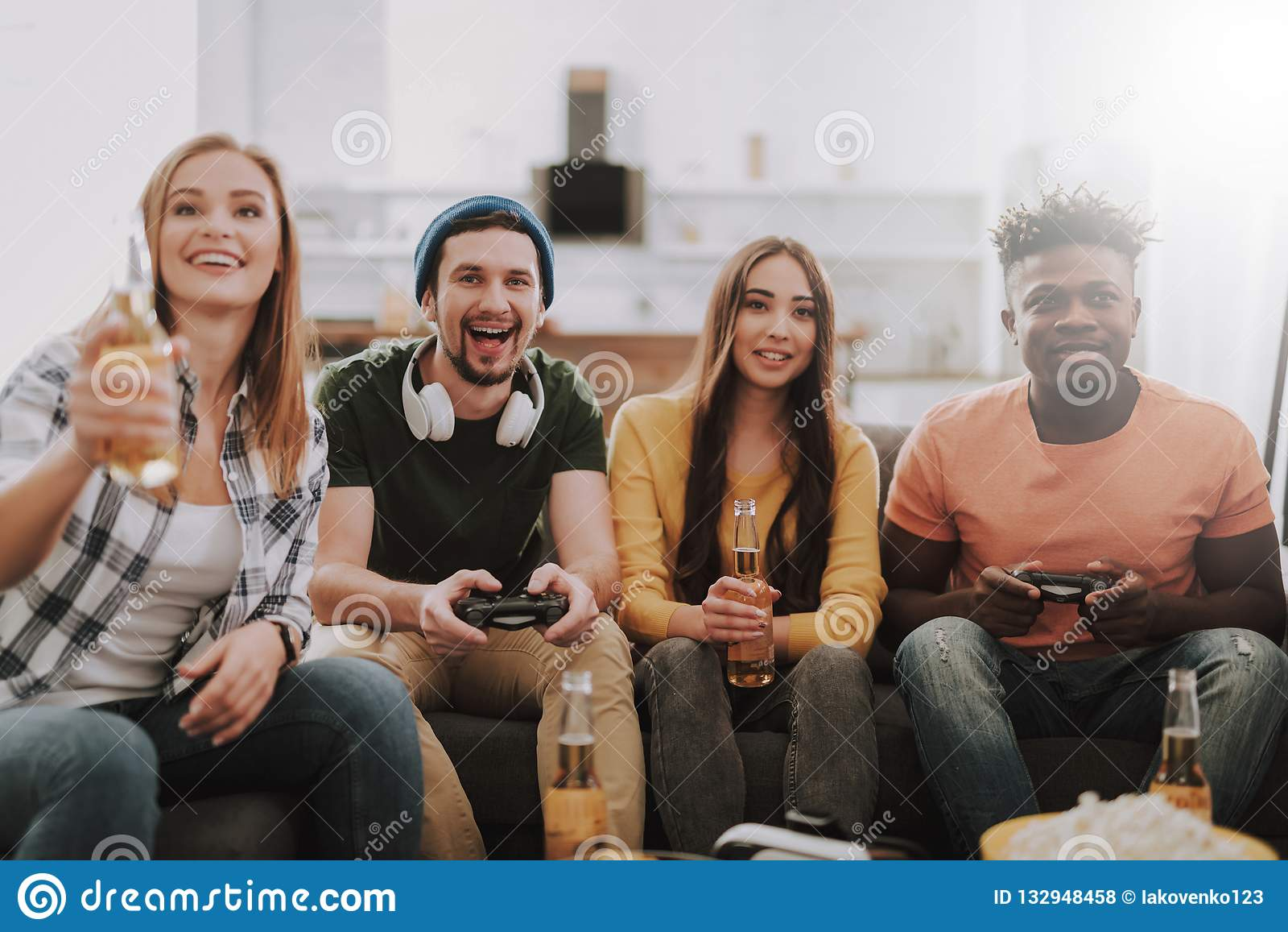Group of friends playing video games and enjoying drinks at home