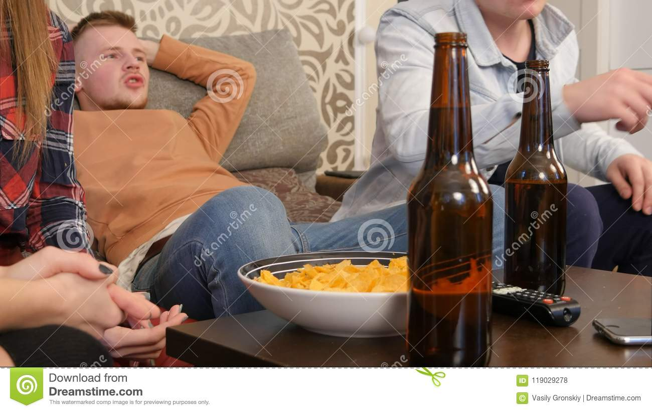 Group of friends sitting on sofa, watching TV together and drinking beer