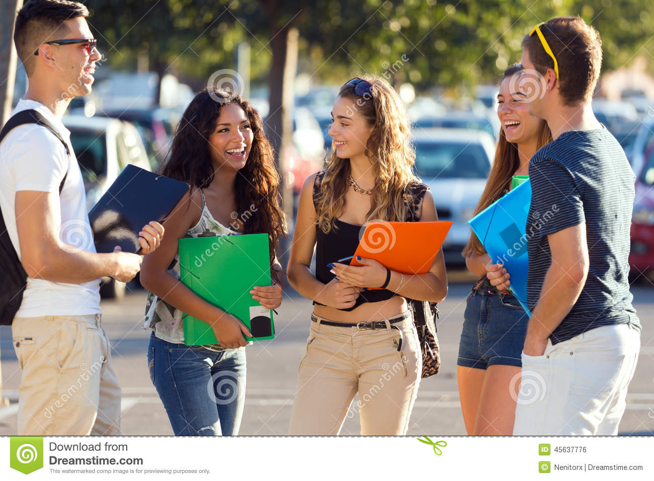 a group of friends talking in the street after class stock