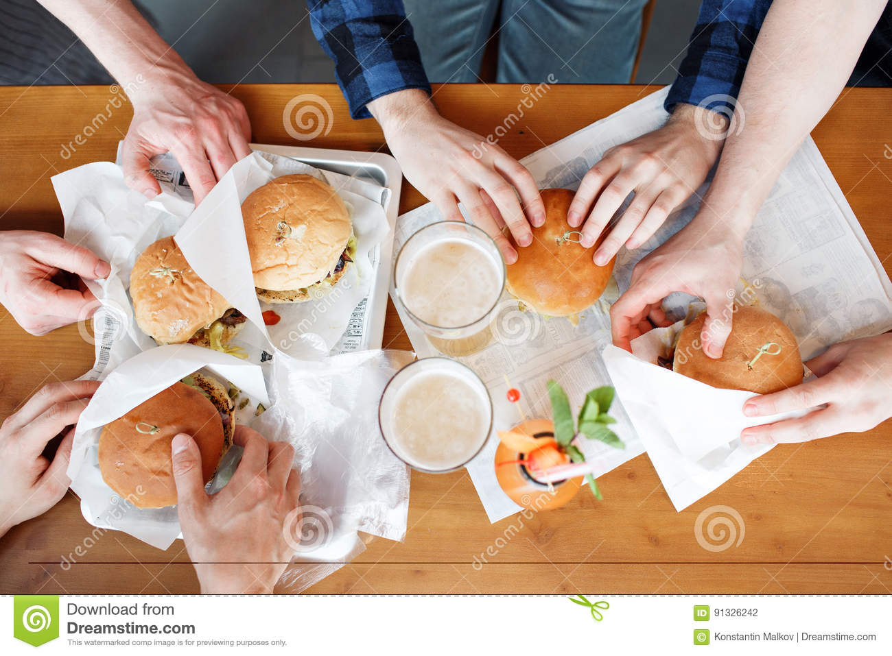Group of friends toasting beer glasses and eating at fast food - Happy people partying and eating in home garden - Young