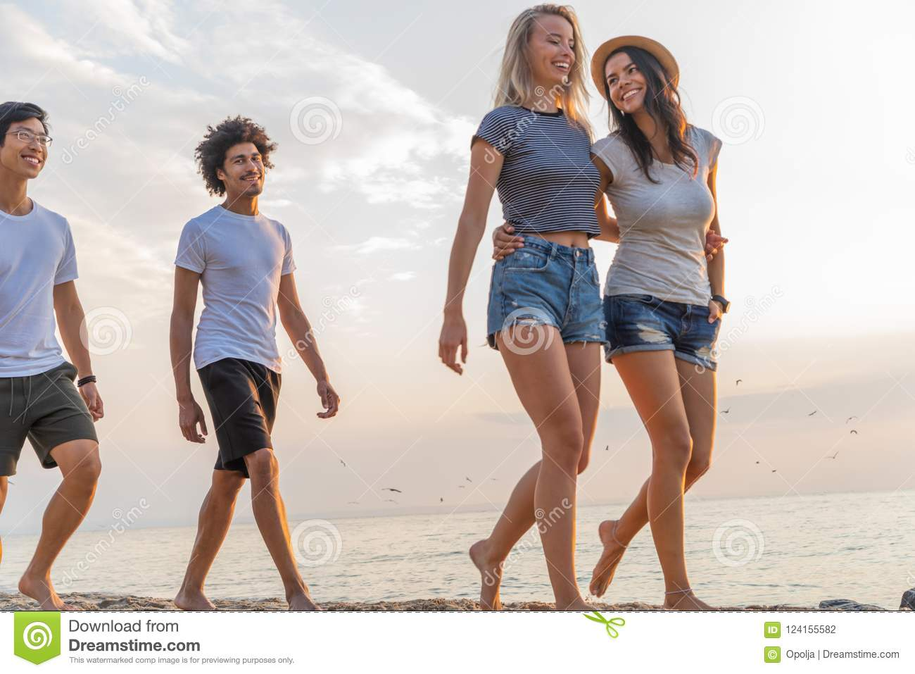 group of friends walking along a beach at summertime happy young