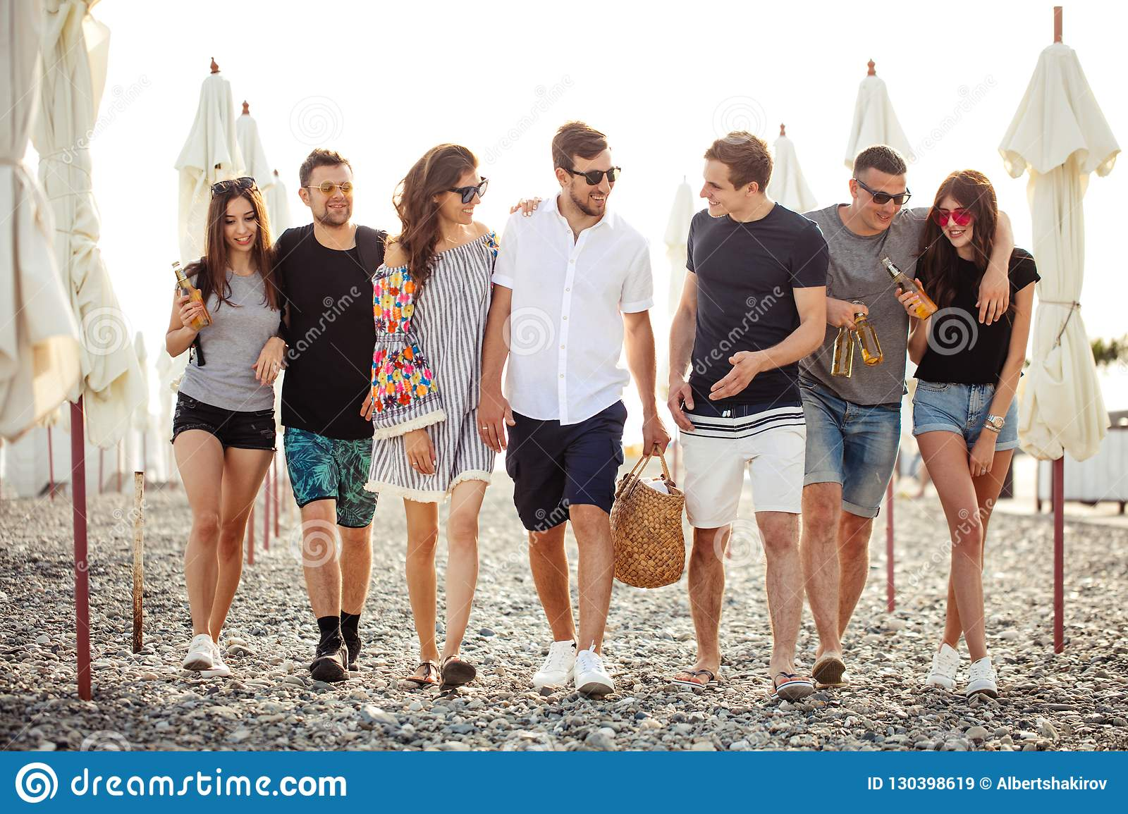 Holidays, vacation. group of friends having fun on beach, walking, drink beer, smiling and hugging