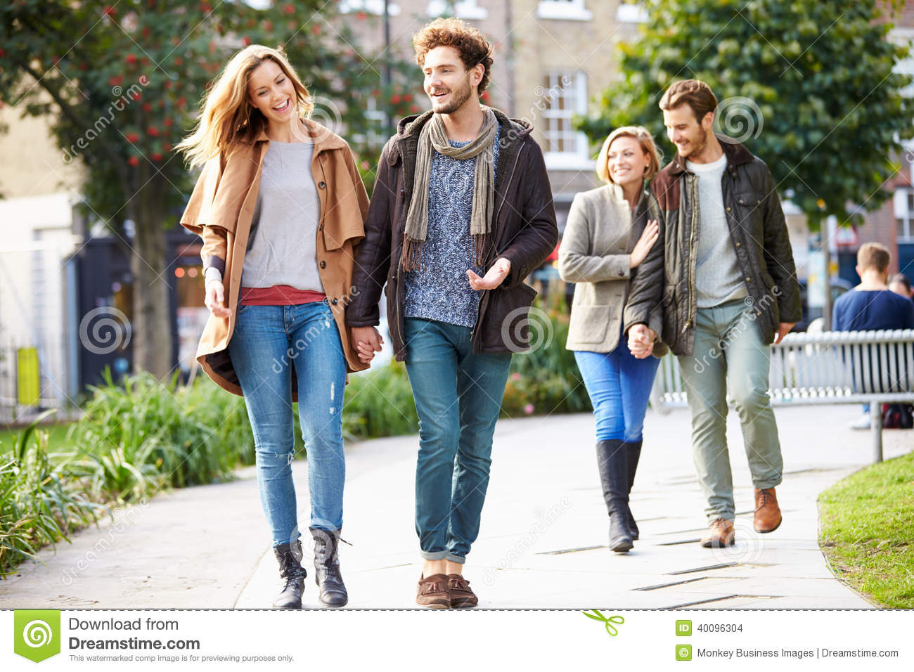 group of friends walking through city park together stock photo