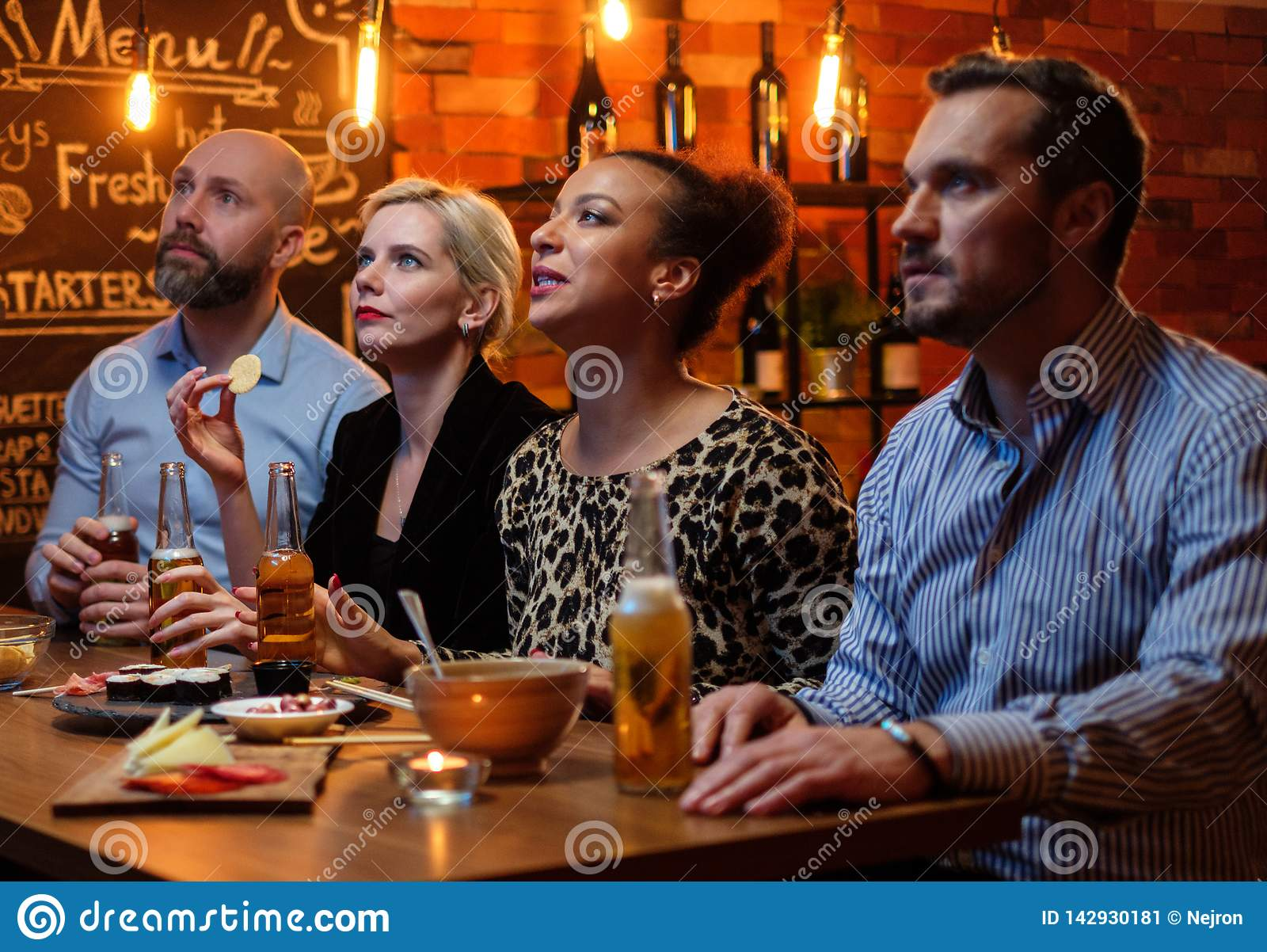 Group Of Friends Watching Tv In A Cafe Behind Bar Counter Stock Image Image Of Restaurant Counter 142930181