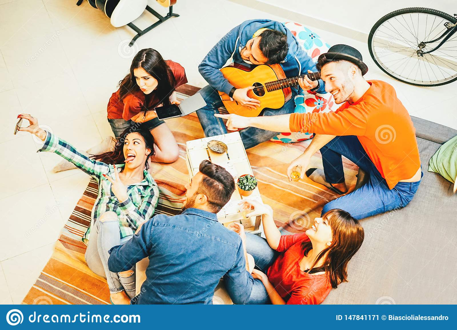 Group of funny friends enjoying together playing music with guitar and taking selfie with mobile phone