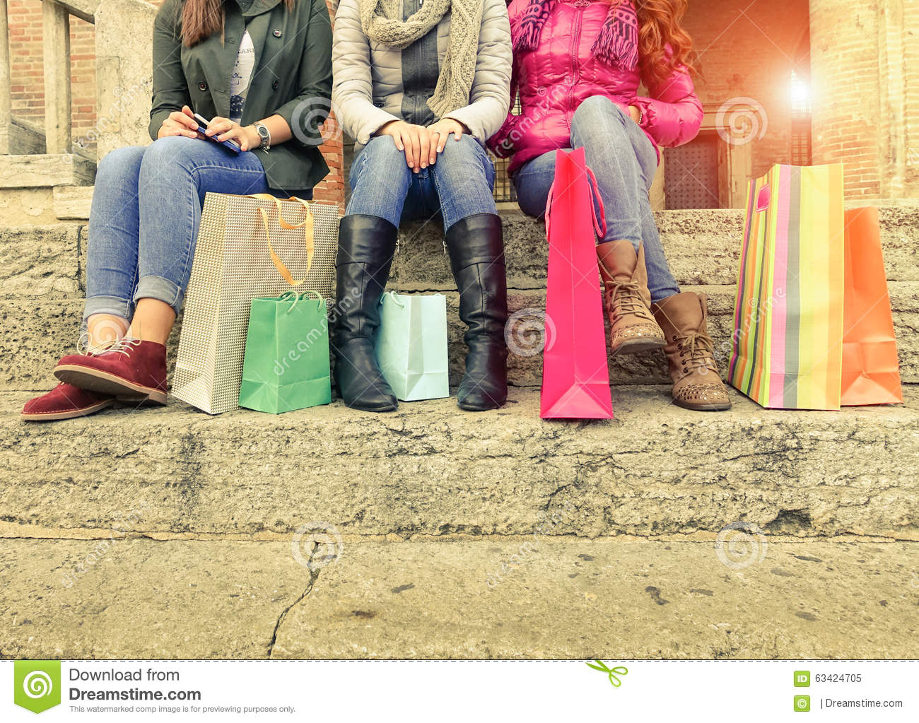 Group girls sitting and chatting after shopping in city