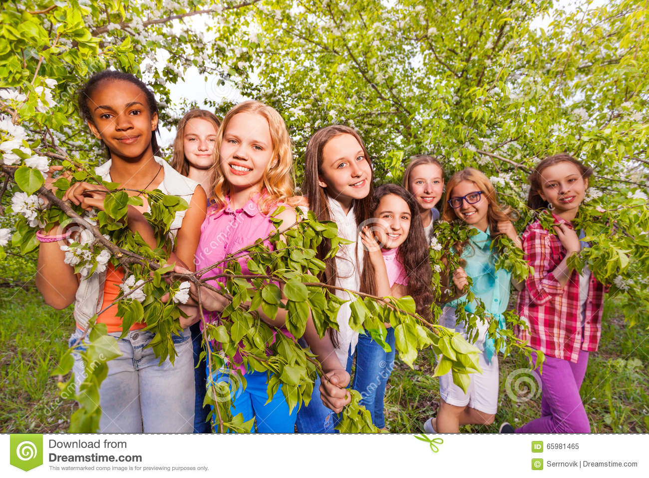 Gardening Group: Group Of Girls In Spring Apple Garden Stock Photo