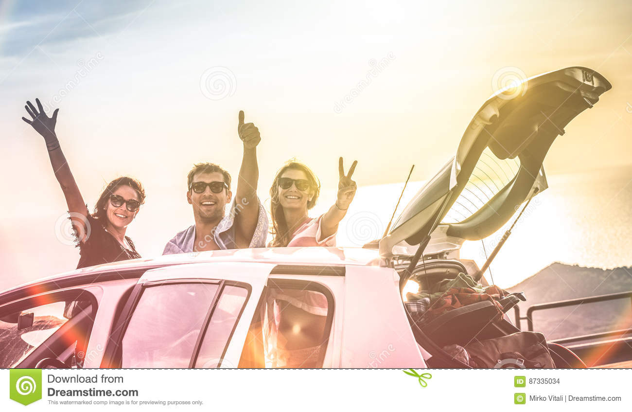Group of happy best friends cheering on car road trip at sunset