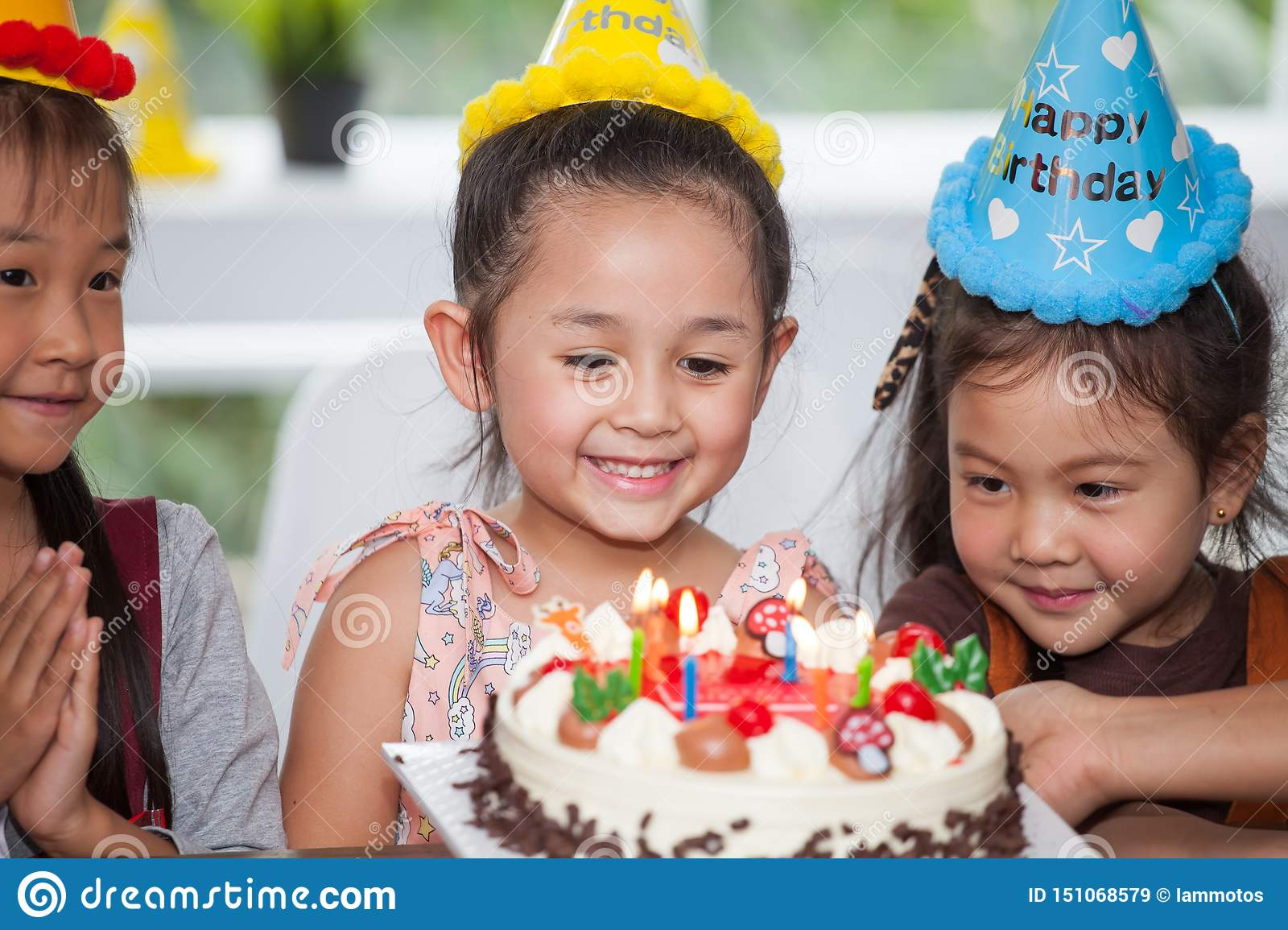 group of happy children girl with hat blowing candles on birthday cake together celebrating in party . adorable kids gathered