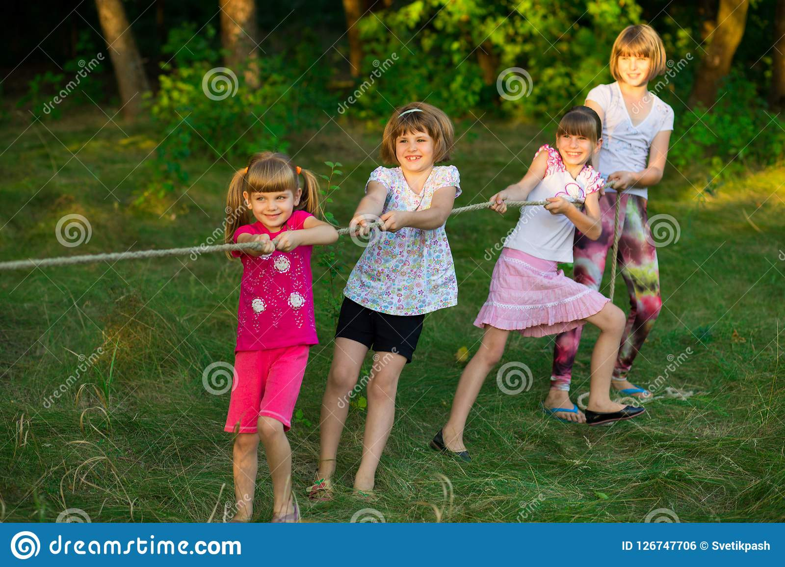 Group of happy children playing tug of war outside on grass. Kids pulling rope at park