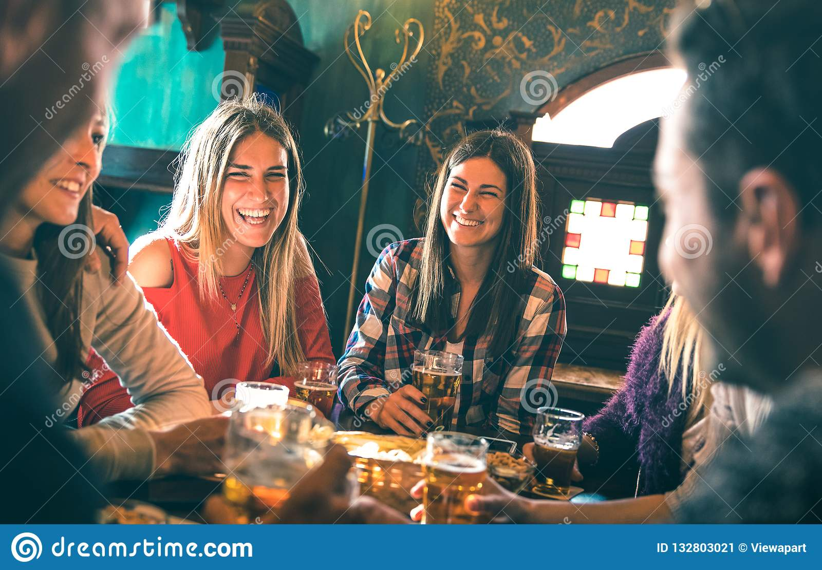 Group of happy friends drinking beer at brewery bar restaurant