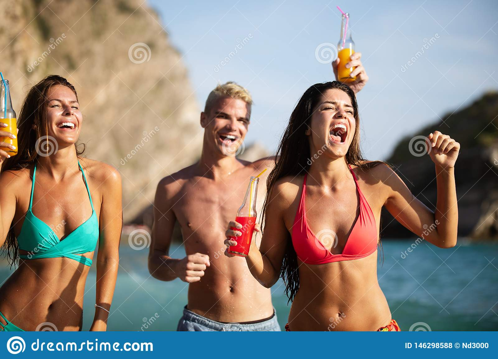 Group of happy friends enjoying the beach at summer