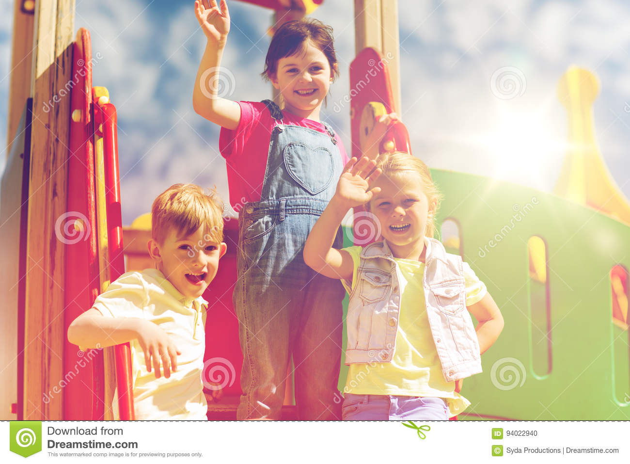 Group of happy kids waving hands on playground